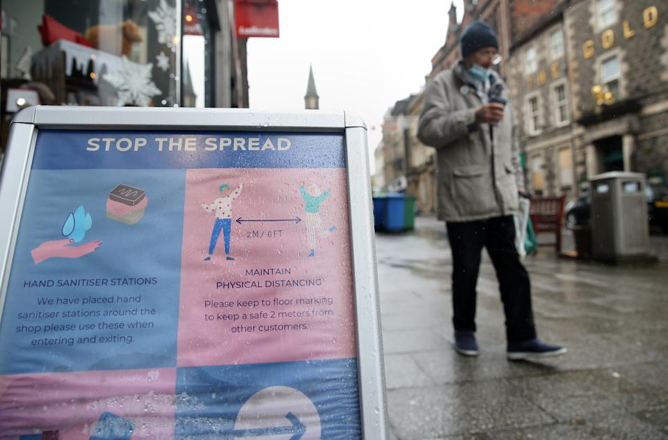 A sign advising customers about the spread of coronavirus outside a shop in Stirling. Scotland is currently using a tier system to try and drive down coronavirus cases.