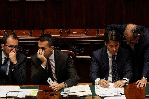 Italian Premier Giuseppe Conte, second from right, flanked by Labour Minister Luigi Di Maio, center, and Justice Minister Alfonso Bonafede, left, talks to Economy Minister Giovanni Trio, ahead of a confidence vote on the government programme, in Rome, Wednesday, June 6, 2018. Conte and his cabinet members are facing a confidence vote at the Lower Chamber of Deputies after winning a confidence vote at the Senate Tuesday night. (AP Photo/Gregorio Borgia)