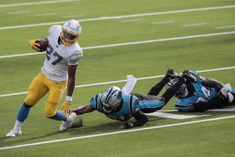 Inglewood, CA, Sunday, September 27, 2020 - Los Angeles Chargers running back Joshua Kelley (27) slips past Carolina Panthers outside linebacker Jeremy Chinn (21) and Carolina Panthers defensive end Efe Obada (94) during a second half drive at SoFi Stadium. (Robert Gauthier/ Los Angeles Times)