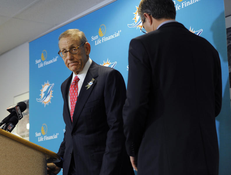 Miami Dolphins owner Stephen Ross, left, and CEO Tom Garfinkel cross paths as they address the media before an NFL football game against the Tampa Bay Buccaneers Monday, Nov. 11, 2013, in Tampa, Fla. (AP Photo/Brian Blanco)