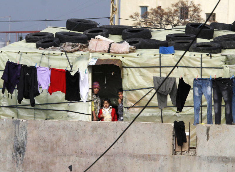 In this on Monday, Feb. 11, 2013 photo, Syrian refugee children who fled their homes with their families due to fighting between rebels and government forces, look outside their tent, in the southern port city of Sidon, Lebanon. According to the United Nations refugee agency, there are now more than 265,000 Syrian refugees scattered across Lebanon, straining services in health, education and housing, pushing up prices and causing friction with Lebanese, some of whom resent their presence and blame them for everything from rising crime to the country's notorious traffic. The issue is particularly sensitive given Lebanon's long and complicated history with tens of thousands of Palestinian refugees who fled to Lebanon with Israel's creation in 1948, as well as Syria's long dominance over Lebanese politics. (AP Photo/Mohammed Zaatari)
