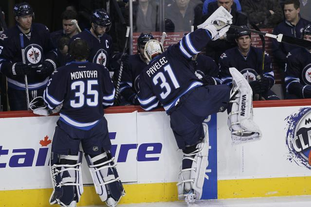 Winnipeg Jets goaltender Ondrej Pavelec (31) climbs over the boards after being pulled during first-period NHL hockey game action against the Minnesota Wild in Winnipeg, Manitoba, Friday, Dec. 27, 2013. (AP Photo/The Canadian Press, John Woods)