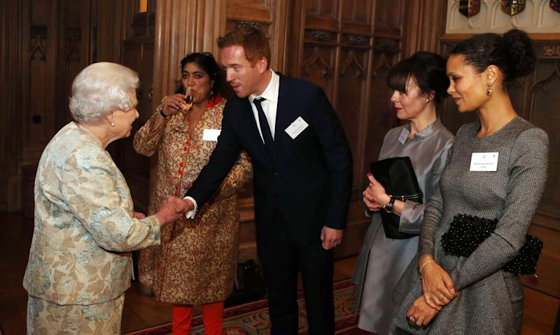 Queen Elizabeth II meets actor Damian Lewis at a reception for the British film industry at Windsor Castle, Thursday April 4, 2013. At left is actress Thandi Newton. (AP Photo/ Steve Parsons, pool)