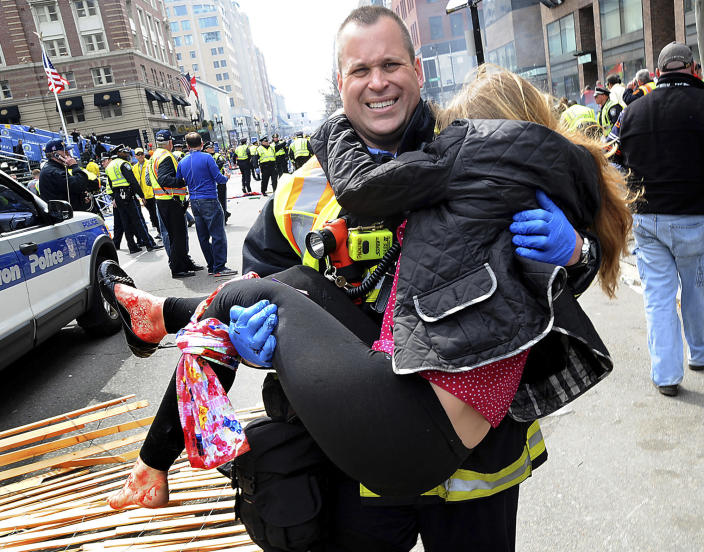 FILE - In this Monday, April 15, 2013 file photo, Boston Firefighter James Plourde carries an injured girl away from the scene after a bombing near the finish line of the Boston Marathon in Boston. As people lay badly bleeding in the smoke of the Boston Marathon bombings, rescuers immediately turned to a millennia-old medical device to save their lives _ the tourniquet. Using belts, shirts and other materials, they tied off bleeding limbs in fast-acting bids to prevent major blood loss, shock and death. Such fast work no doubt saved many lives, doctors at Boston area hospitals said. (AP Photo/MetroWest Daily News, Ken McGagh, File) MANDATORY CREDIT