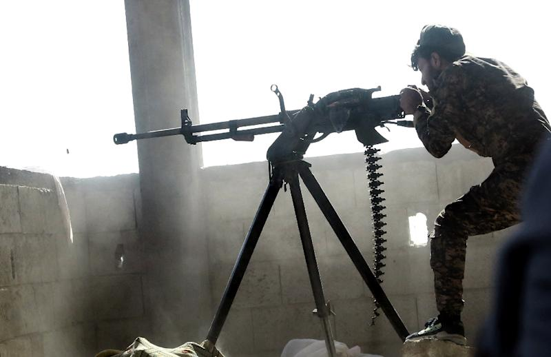 A fighter of the US-backed Syrian Democratic Forces fires a machine gun during their advance into the Islamic State group stronghold of Raqa on June 21, 2017