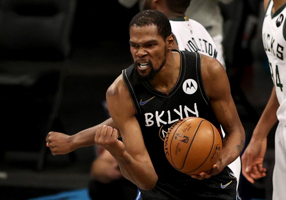 Kevin Durant pumps his fist as he celebrates after being fouled.