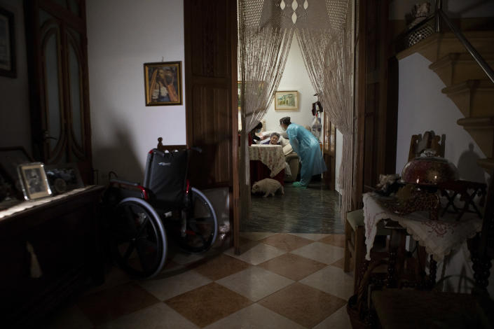 Nurse Pilar Rodríguez speaks with Paula Serra Caldes, 93, as she explains to her about vaccination against COVID-19, in the town of Sa Pobla on the Spanish Balearic Island of Mallorca, Spain, Friday, April 30, 2021. While thousands flock daily at health clinics and ad-hoc vaccination points across Spain, health workers also fan out across the country to take shots to some of those who are the most vulnerable to the coronavirus. (AP Photo/Francisco Ubilla)