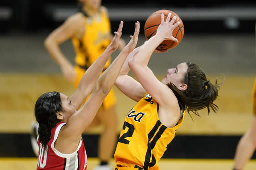 Iowa guard Caitlin Clark shoots over Ohio State guard Braxtin Miller during overtime in an NCAA college basketball game Wednesday, Jan. 13, 2021, in Iowa City, Iowa. Clark, one of the top scorers in the nation, has been named the Big Ten's player of the week three times this season and has won the conference's freshman of the week honor six times. (AP Photo/Charlie Neibergall)