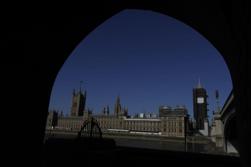 Britain's Houses of Parliament is seen through an archway alongside the River Thames as the country is in lockdown to help curb the spread of coronavirus, in London, Tuesday, April 21, 2020. Britain's Parliament is going back to work, and the political authorities have a message for lawmakers: Stay away. U.K. legislators and most parliamentary staff were sent home in late March as part of a nationwide lockdown to slow the spread of the new coronavirus. With more than 16,500 people dead and criticism growing of the government's response to the pandemic, legislators are returning Tuesday — at least virtually — to grapple with the crisis. (AP Photo/Kirsty Wigglesworth)
