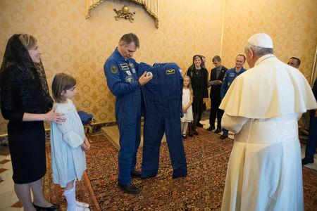 Pope Francis receives an astronaut suit from Italian astronaut Paolo Nespoli during a private meeting with crew members of the ISS 53 space mission at the Vatican June 8, 2018.  Vatican Media/Handout via REUTERS