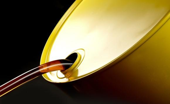 Oil pours from a golden drum