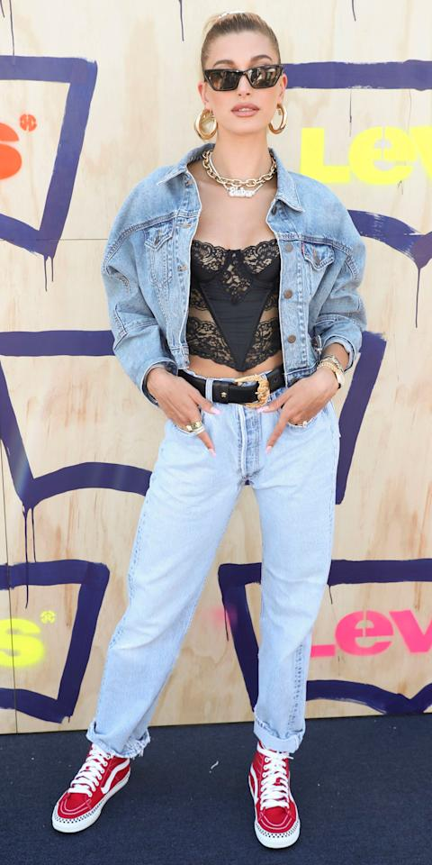 <p>As the new face of Levi's 501, Hailey Baldwin showed up at the brand's Coachella bash, giving her denim a daring twist with a vintage Dior corset, Jennifer Fisher hoops, a Jack Vartanian chain necklace and a pair of red Vans sneakers.</p>