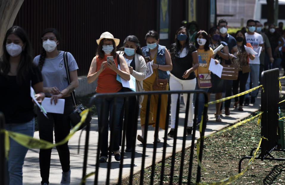 Educators stand in line as they wait to be vaccinated with the CanSino COVID-19 vaccine, on the grounds of the National Polytechnic Institute, in Mexico City, Tuesday, May 18, 2021. Mexico is mounting a final push to get all of the country's school teachers vaccinated so that it can reopen schools, perhaps by June. (AP Photo/Marco Ugarte)