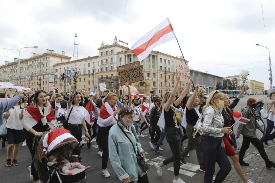 """Women with old Belarusian national flags and a poster reads """"I will survive Lukashenka"""" march during an opposition rally to protest the official presidential election results in Minsk, Belarus, Saturday, Sept. 5, 2020. Women's marches and demonstrations have become a regular feature of the four weeks of protest that have shaken Belarus following a disputed election that gave Belarusian President Alexander Lukashenko a sixth term in office. (AP Photo)"""