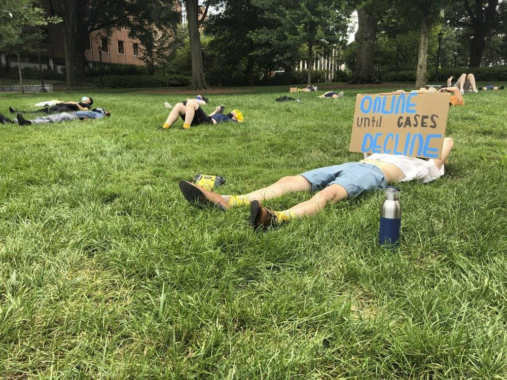 "A protester holds a sign opposing in-person classes Monday, August 17, 2020, at a ""die-in"" at Georgia Tech in Atlanta. (AP Photo/Jeff Amy)"