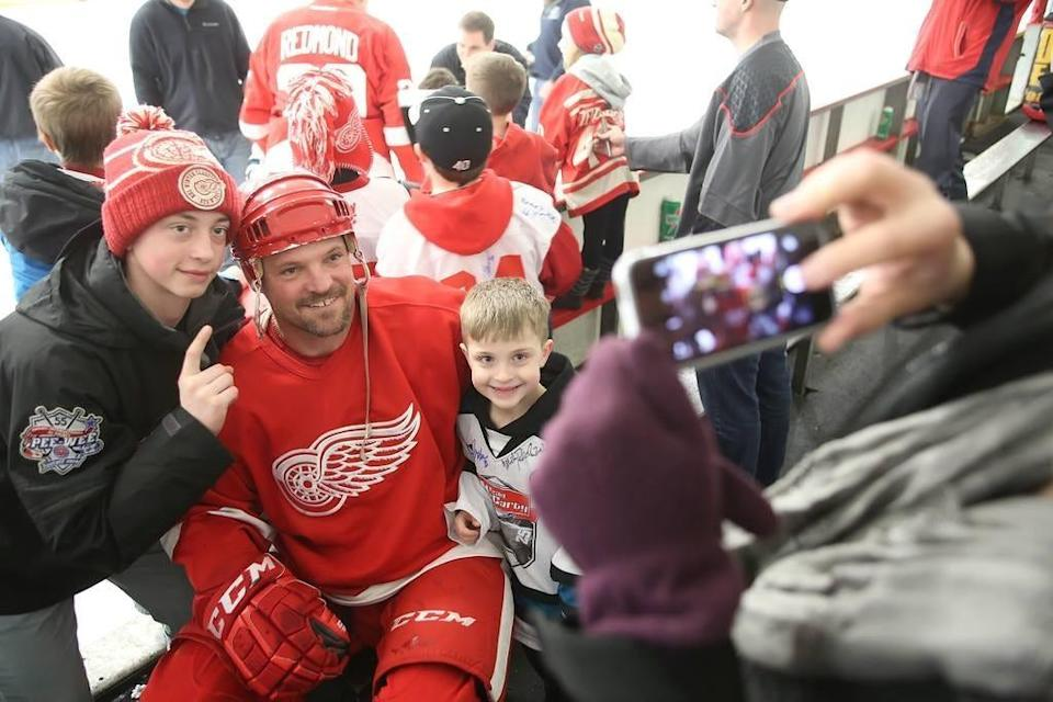 Joe Kocur poses with fans at a Detroit Red Wings alumni hockey game.