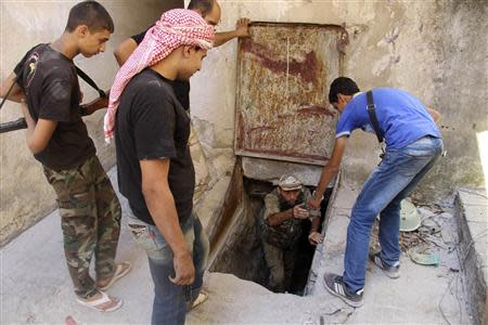 A Free Syrian Army fighter helps a fellow fighter get out of a tunnel in the old city of Aleppo September 10, 2013. REUTERS/Molhem Barakat