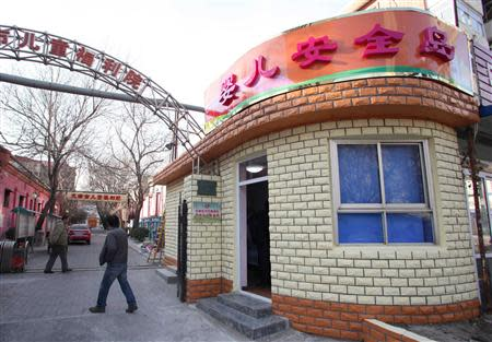 "People walk past next to a baby hatch named ""baby safety island"" at the Tianjin Institute of Children's Welfare, in Tianjin municipality, December 27, 2013. REUTERS/Stringer"