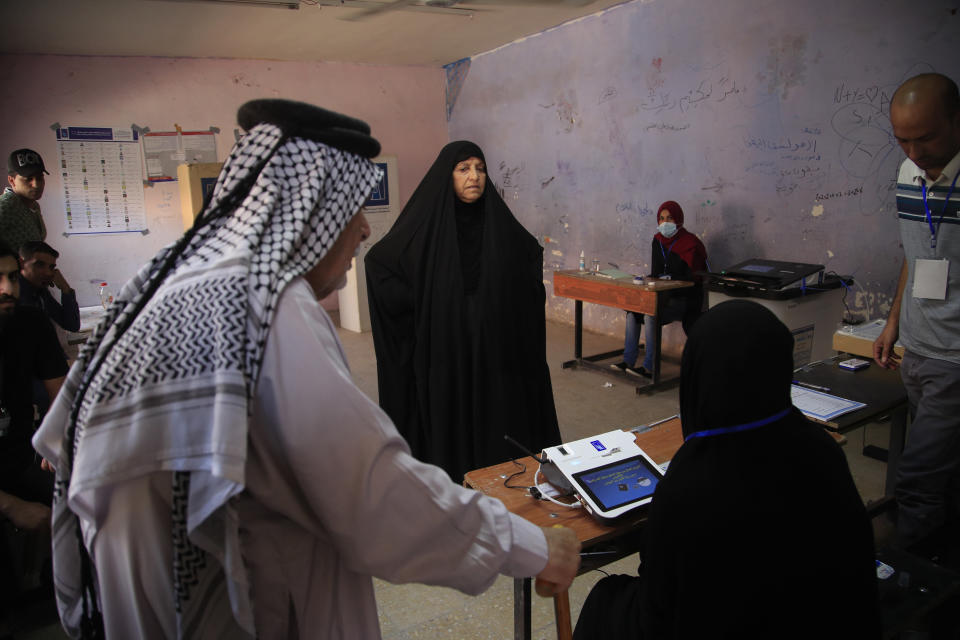 Iraqis gather to cast their vote at a ballot station in the country's parliamentary elections in Baghdad, Iraq, Sunday, Oct. 10, 2021. Iraq closed its airspace and land border crossings on Sunday as voters headed to the polls to elect a parliament that many hope will deliver much needed reforms after decades of conflict and mismanagement.. (AP Photo/Hadi Mizban)