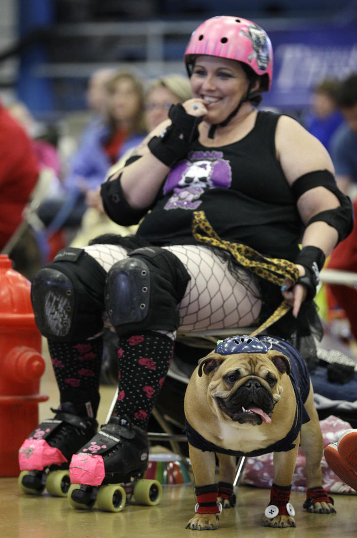 Leanne Sergio, of Ankeny, Iowa, sits with her dog Mya during the 33rd annual Drake Relays Beautiful Bulldog Contest Monday, April 23, 2012, in Des Moines, Iowa. The pageant kicks off the Drake Relays festivities at Drake University where a bulldog is the mascot. (AP Photo/Charlie Neibergall)