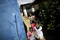 """Rosana Vieira Alves carries her four-month-old daughter Luana Vieira, who was born with microcephaly, while taking her daughters Laiane Sophia (L) and Vitoria Evillen to their school in Olinda, Brazil, February 4, 2016. REUTERS/Ueslei Marcelino/File Photo SEARCH """"ZIKA"""" FOR THIS STORY. SEARCH """"WIDER IMAGE"""" FOR ALL STORIES."""