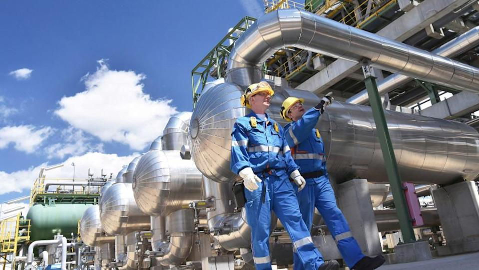 Group of industrial workers in a refinery - oil processing equipment and machinery