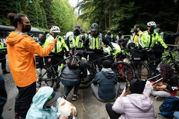 Police attempt to move climate change activists away from the Lions Gate Bridge in Vancouver, B.C., on Monday, May 3, 2021. (Maggie MacPherson/CBC - image credit)