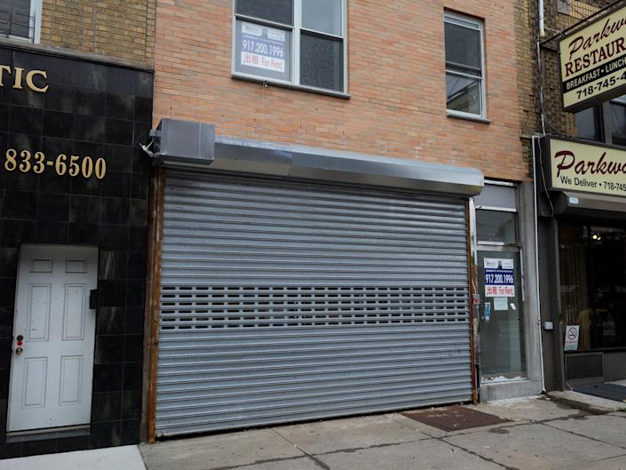 A grey gate covers an empty storefront.