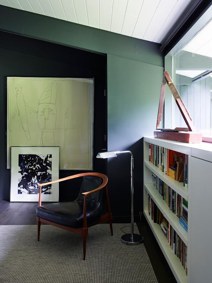 """<div class=""""caption""""> In the library, a drawing by James Brown and a work on paper by Clarence Van Duzer pop against a wall painted in <a href=""""https://www.benjaminmoore.com/en-us"""" rel=""""nofollow noopener"""" target=""""_blank"""" data-ylk=""""slk:Benjamin Moore"""" class=""""link rapid-noclick-resp"""">Benjamin Moore</a>'s Notre Dame. The vintage chair is from <a href=""""https://www.averydash.com/"""" rel=""""nofollow noopener"""" target=""""_blank"""" data-ylk=""""slk:Avery & Dash Collections"""" class=""""link rapid-noclick-resp"""">Avery & Dash Collections</a>. </div>"""