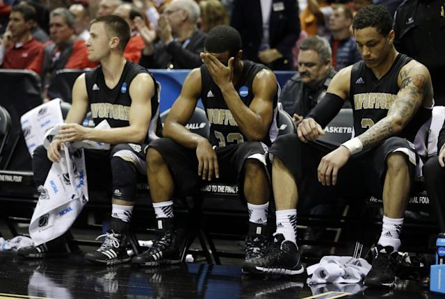Wofford's Eric Garcia, left, Spencer Collins, and Karl Cochran react on the bench during the second half of a second round NCAA college basketball tournament game Thursday, March 20, 2014, in Milwaukee. Michigan won 57-40. (AP Photo/Morry Gash)
