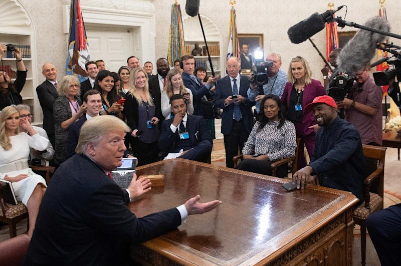 US President Donald Trump meets with rapper Kanye West (R red cap) in the Oval Office of the White House in Washington, DC, on October 11, 2018