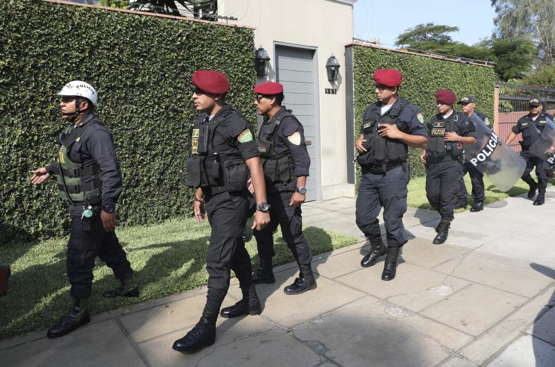 Peruvian police arrive to take position outside the residence of Peru's former President Pedro Pablo Kucyznksi, in Lima, Peru, Wednesday, April 10, 2019. A judge in Peru has ordered the detention for 10 days of the former leader as part of a money laundering probe into his consulting work for the company at the heart of Latin America's biggest graft scandal. (AP Photo/Martin Mejia)