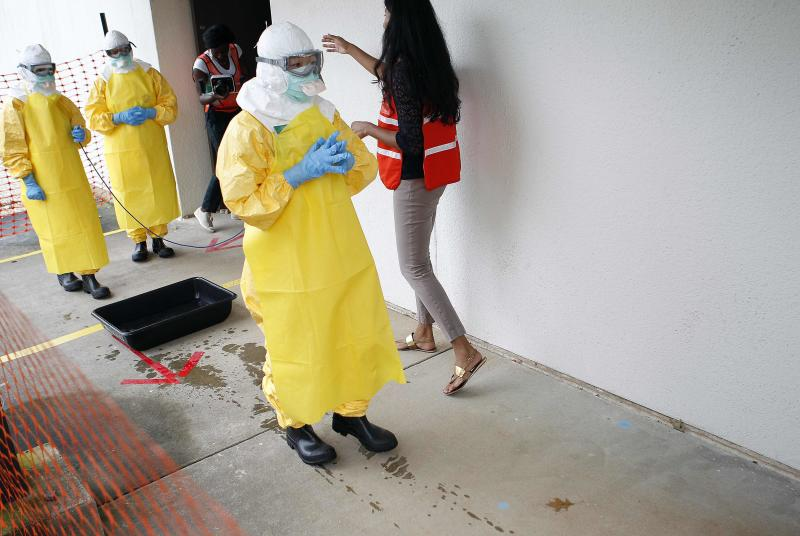 Kwan Keu Lai (C), a doctor with Beth Israel Deaconess Medical Center, waits as she receives guidance from Centers for Disease Control and Prevention (CDC) instructor Rupa Narra (R) along with other health care workers, in preparation for the response to the current Ebola outbreak, during a CDC safety training course in Anniston, Alabama, October 6, 2014. Developed by the U.S. CDC as part of its escalated response to the worst Ebola outbreak on record, the three-day program teaches how to safely treat patients in West Africa with the virus, which causes fever and bleeding and is often fatal. The course, held at an old Army base in Anniston, Alabama, will provide instruction for about 40 people a week through January. Picture taken October 6, 2014.  REUTERS/Tami Chappell  (UNITED STATES - Tags: HEALTH DISASTER POLITICS EDUCATION)