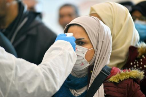 An Iraqi woman's temperature is taken upon her return from Iran at the Najaf International Airport on February 21