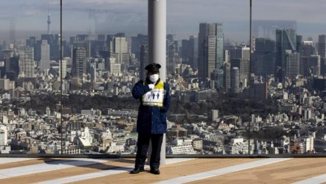 A skyline of Tokyo is seen from the Shibuya Sky observation deck as a security stands guard in Tokyo on February 2, 2021 as Japan extended a coronavirus state of emergency in several parts of the country, with less than six months to go until the pandemic-postponed Olympics. Image: AFP