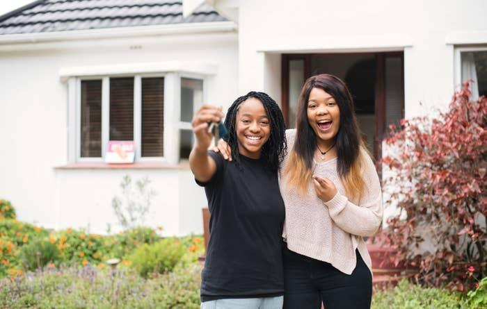 Two happy young women showing off the keys to a new house