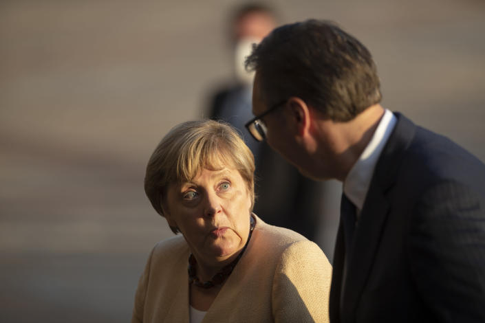 German Chancellor Angela Merkel, left, is accompanied by Serbia's president Aleksandar Vucic in Belgrade, Serbia, Monday, Sept. 13, 2021. Merkel is on a farewell tour of the Western Balkans, as she announced in 2018 that she wouldn't seek a fifth term as Germany's Chancellor. (AP Photo/Marko Drobnjakovic)