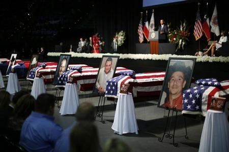 Portraits of twelve who died in the fertilizer plant explosion in West, Texas, are pictured alongside their coffins as U.S. President Barack Obama delivers remarks during a memorial ceremony held at Baylor University in Waco