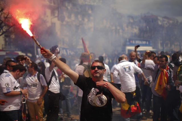 A Real supporter holds a flare, as Real Madrid supporters gather, prior to the Champions League final soccer match between Atletico Madrid and Real Madrid in downtown Lisbon, Portugal, Saturday, May 24, 2014. (AP Photo/Andres Kudacki)