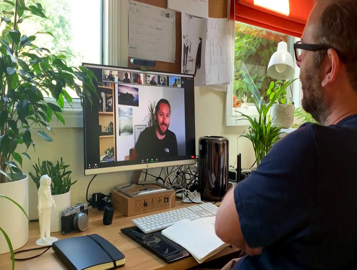 """This July 2020 photo taken from video released by Locksmith Animation shows art director Justin Hutchinson-Chatburn, right, communicating on his computer during the filming of a video diary. The London animation studio Locksmith had been in production on """"Ron's Gone Wrong"""" for more than two years before the pandemic hit. Suddenly, animators found themselves on lockdown wrestling with glitchy technology. Hutchinson-Chatburn said it's remarkable that animation is """"thriving and surviving"""" during the pandemic, but he's hoping to gather with work colleagues in person soon. (Locksmith Animation via AP)"""
