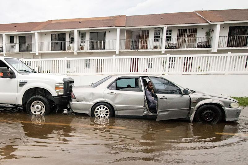 A truck pushes a stalled car through a flooded street on Monday after Hurricane Dorian ripped through Nassau, the capital of the Bahamas.