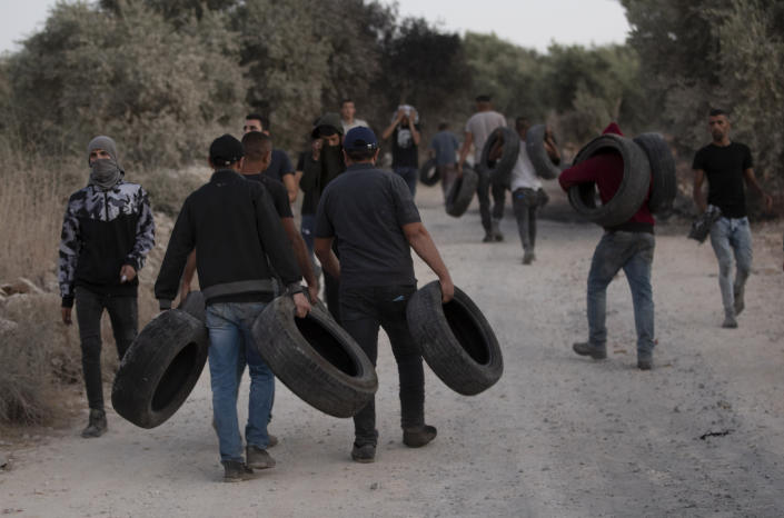 Palestinian demonstrators hold tires during a demonstration against the West Bank Jewish settlement outpost of Eviatar that was rapidly established last month, at the Palestinian village of Beita, near the West Bank city of Nablus, Sunday, June 27, 2021. The Palestinians say it was established on their farmland and fear it will grow and merge with other large settlements in the area. (AP Photo/Majdi Mohammed)
