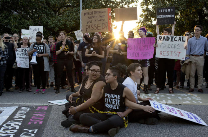 <p>From left, demonstrators Jess Jude, Loan Tran and Noah Rubin-Blose sit chained together in the middle of the street during a protest against House Bill 2 on March 24, 2016, outside of the governor's Executive Mansion on North Blount Street in downtown Raleigh, N.C.<i> (Jill Knight/Raleigh News & Observer/TNS via Getty Images)</i></p>