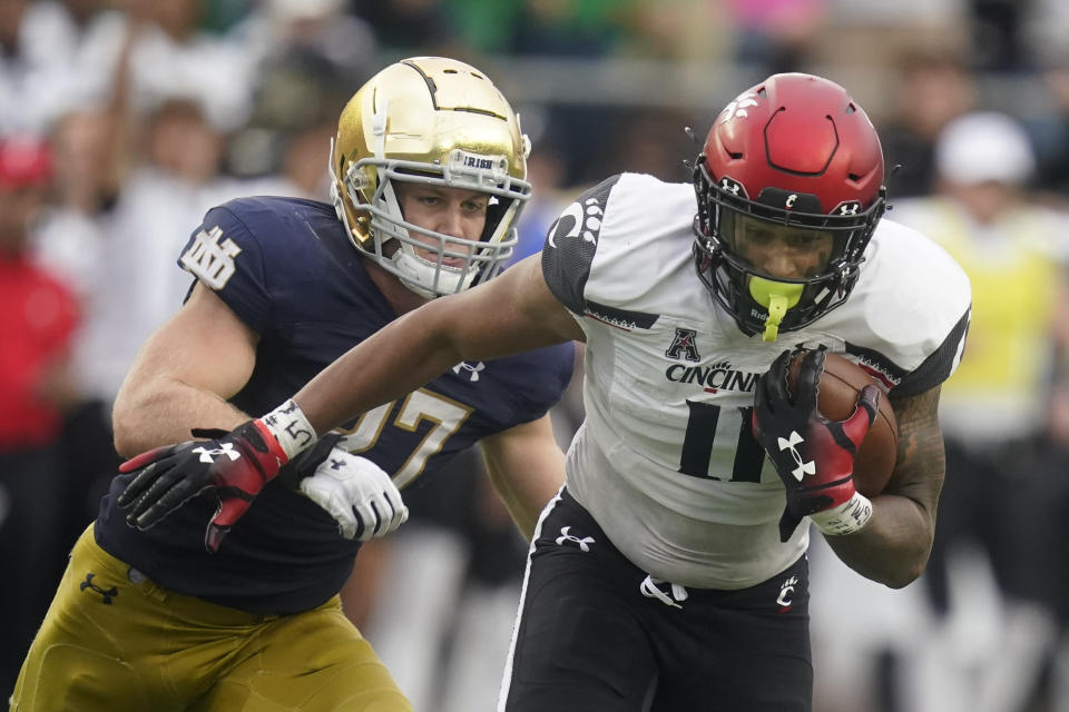 Cincinnati's Leonard Taylor (11) is chased by Notre Dame's JD Bertrand (27) during the second half of an NCAA college football game, Saturday, Oct. 2, 2021, in South Bend, Ind. Cincinnati won 24-13. (AP Photo/Darron Cummings)