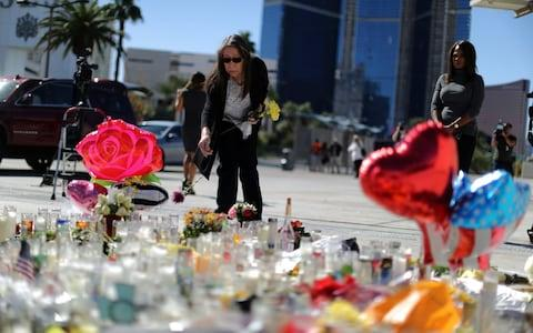 A woman leaves flowers at a makeshift memorial on the Las Vegas Strip - Credit: Reuters