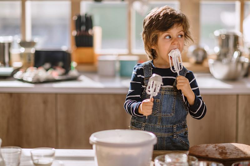 Cute Kid Tasting Whipped Cream of Egg Beater In Kitchen, Making Adorable Funny Faces in Manner of Sweet Taste