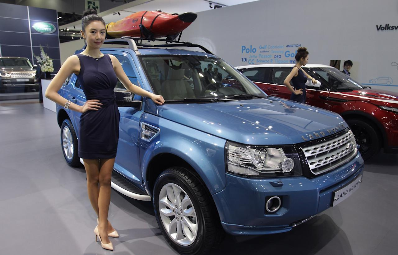 GOYANG, SOUTH KOREA - MARCH 28:  A Model poses next to a Land Rover at the Seoul Motor Show 2013 on March 28, 2013 in Goyang, South Korea. The Seoul Motor Show 2013 will be held in March 29-April 7, featuring state-of-the-art technologies and concept cars from global automakers. The show is its ninth since the first one was held in 1995. About 384 companies from 14 countries, including auto parts manufacturers and tire makers, will set up booths to showcase trends in their respective industries, and to promote their latest products during the show.  (Photo by Chung Sung-Jun/Getty Images)