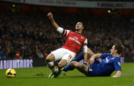Cardiff City's Ben Turner (R) is booked for this foul on Arsenal's Theo Walcott during their English Premier League soccer match at the Emirates Stadium in London January 1, 2014. REUTERS/Dylan