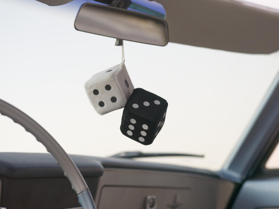 Dice hanging from a rear view car mirror. Source: Getty Images
