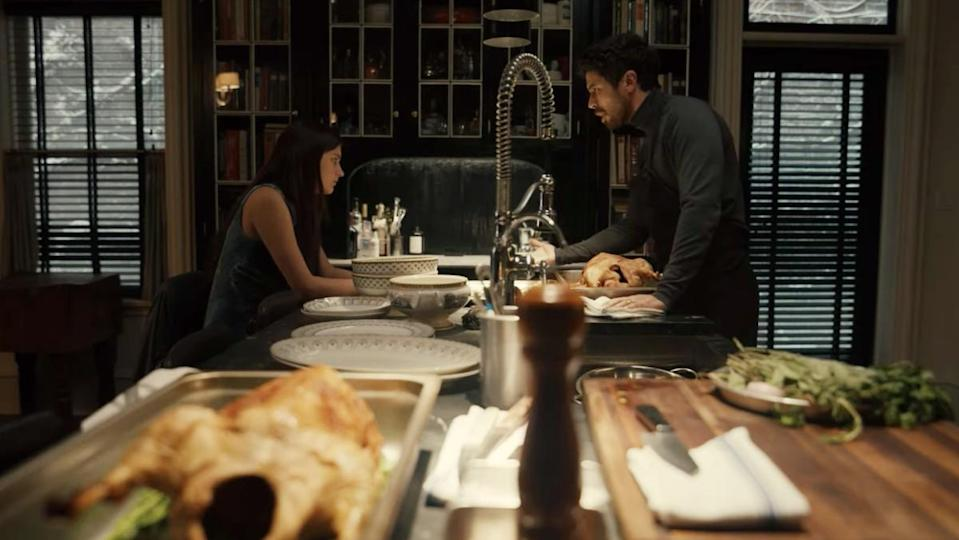 Leanne and Sean stare at each other over the kitchen island in a scene from Apple TV+'s horror series Servant.